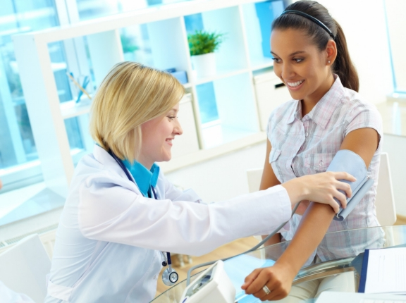 woman getting her blood pressure checked by a doctor in a bright room