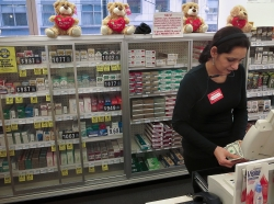 A cashier in front of shelves full of cigarettes at a CVS store