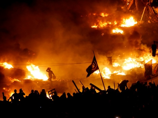 Anti-government protesters stand behind burning barricades in Kiev's Independence Square February 19, 2014