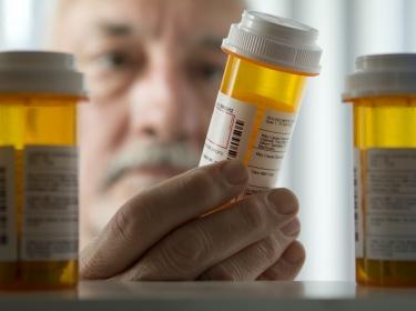 man examining pill bottle
