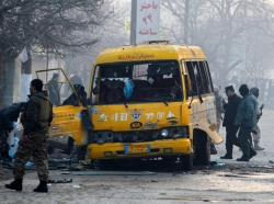 Afghan policemen inspect the wreckage of a bus hit by a suicide attack in Kabul claimed by the Taliban