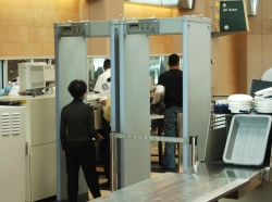 airport security check with passenger walking through metal detector
