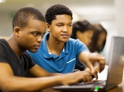 two male students looking at a laptop