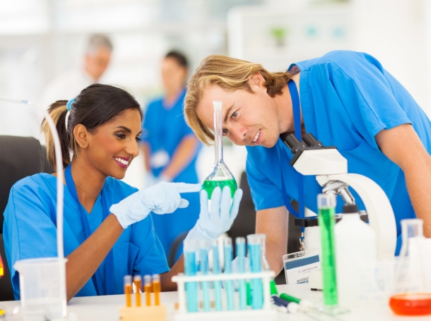 two scientists studying various colored substances in a laboratory