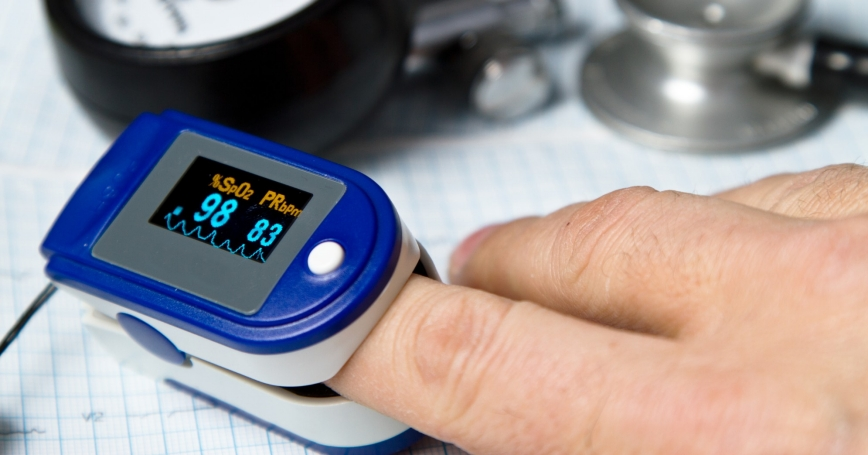 A pulse oximeter used to measure pulse rate and oxygen levels with Sphygmomanometer and medical stethoscope and ECG background