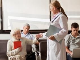doctor greeting elderly patient in waiting area
