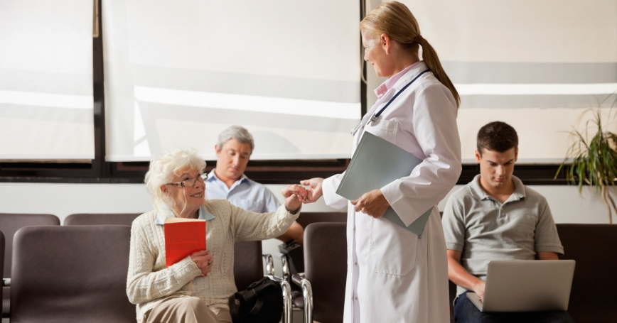 doctor greeting elderly patient in waiting area