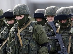 Uniformed men, believed to be Russian servicemen, near a Ukrainian military base in the village of Perevalnoye