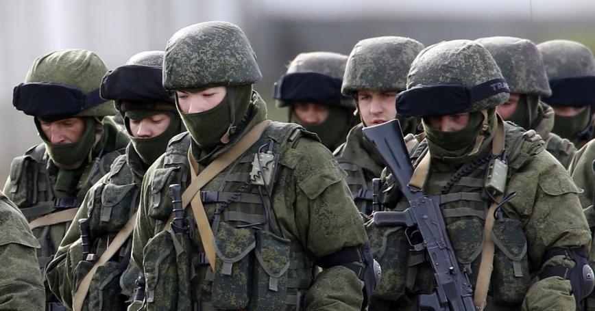 Uniformed men, believed to be Russian servicemen, near a Ukrainian military base in the village of Perevalnoye
