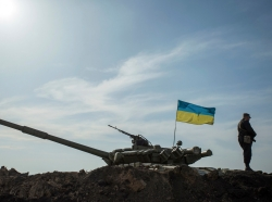 A soldier stands guard near a tank position close to the Russian border near the Ukrainian city of Kharkiv