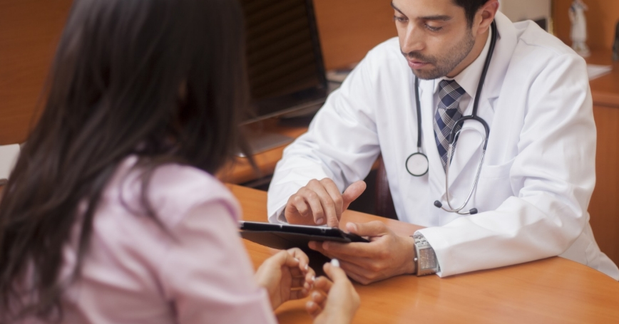doctor reviewing a patient's chart with her on a tablet