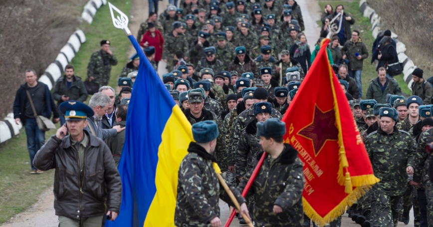 Ukrainian servicemen carry flags as they leave Belbek airport in the Crimea region March 4, 2014. A column of unarmed Ukrainian servicemen arrived at the base for negotiations with Russian troops.