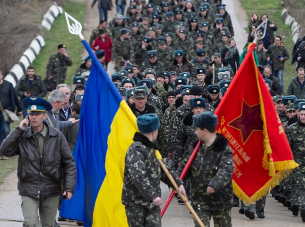 Ukrainian servicemen carry flags as they leave Belbek airport in the Crimea region March 4, 2014. A column of unarmed Ukrainian servicemen arrived at the base for negotiations with Russian troops on Tuesday.