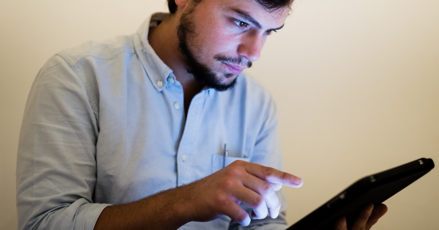 man using and illuminated by the light of tablet