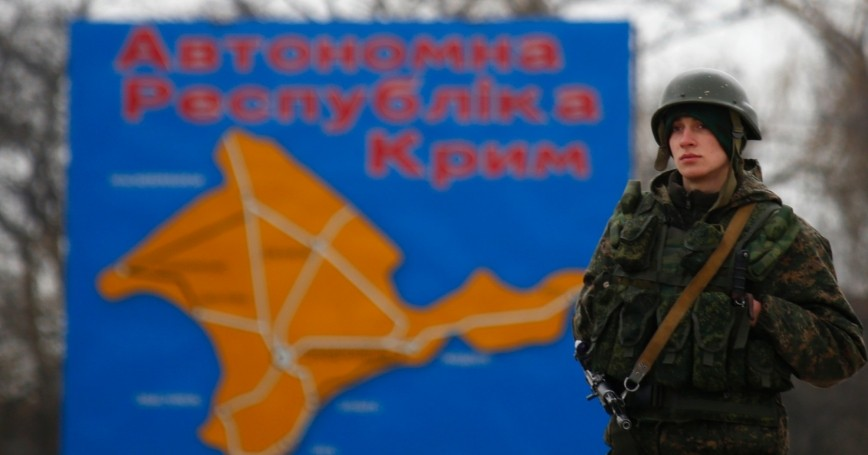 A Russian serviceman stands on duty near a map of the Crimea region near the city of Kerch March 4, 2014