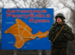 A Russian serviceman stands on duty near a map of the Crimea region near the city of Kerch March 4, 2014. President Vladimir Putin ordered troops involved in a military exercise in western Russia back to base on Tuesday in an announcement that appeared intended to ease East-West tension over fears of war in Ukraine.