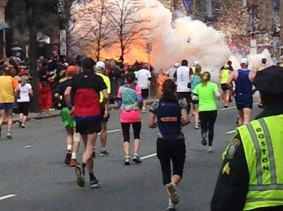 Runners continue to run towards the finish line of the Boston Marathon as an explosion erupts on April 15, 2013
