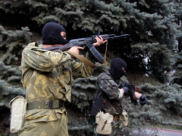 Pro-Russian armed men level automatic rifles near the local police headquarters in Luhansk, eastern Ukraine, April 29, 2014