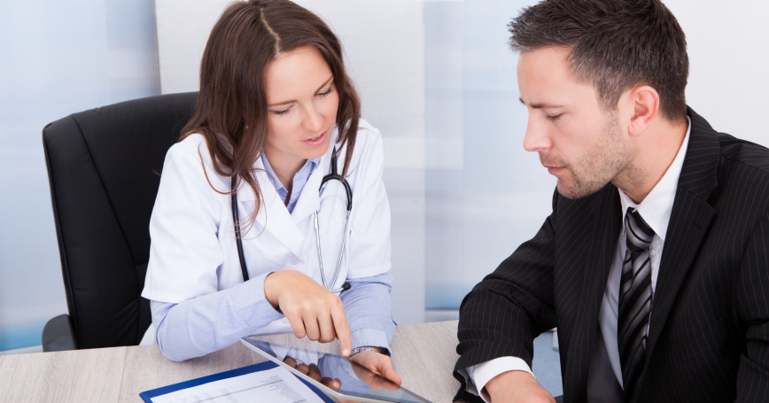 a doctor discussing a patient's chart on a tablet