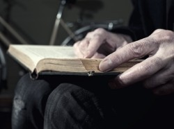 a man holding a book on his lap