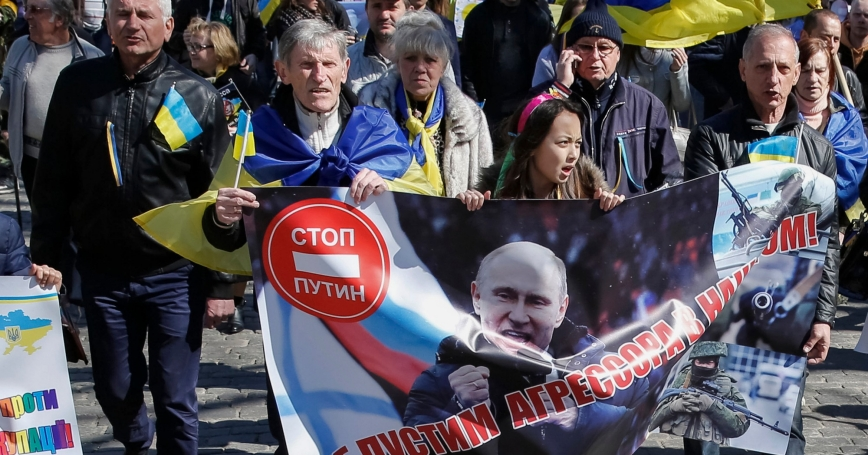 """People rally against the annexation of Crimea by Russia, in Odessa, Ukraine. The banner with a portrait of Putin reads: """"Will not let aggressor to our house."""""""
