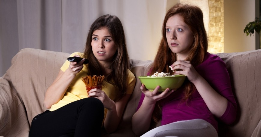 two young women watching something scary on TV and eating popcorn