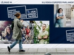 A woman walks past European Parliament election campaign posters in Vilnius