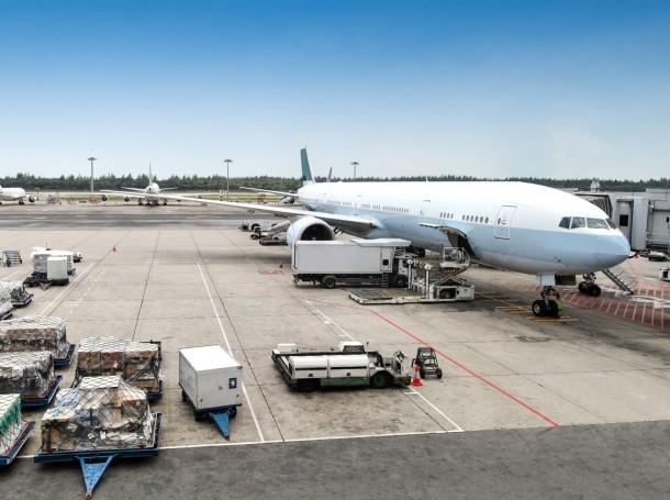 A commercial aircraft being serviced at an airport terminal