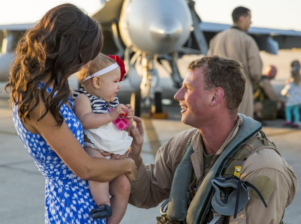 A Marine with Marine All-Weather Fighter Attack Squadron 533 smiles at his daughter after returning from a deployment