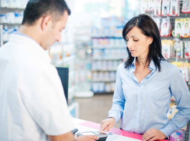a worried-looking woman paying for her prescription at a pharmacy