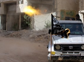 A member of the Islamist Syrian rebel group Jabhat al-Nusra fires during clashes with Syrian forces near Damascus