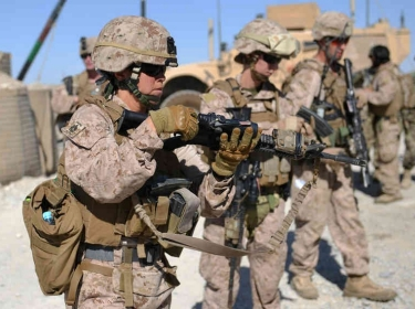 Marines check their rifles after a patrol with Afghan soldiers in Helmand Province, Afghanistan
