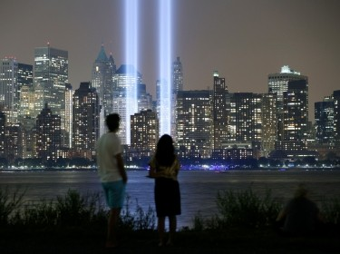 The Tribute in Light is illuminated on the skyline of New York's Lower Manhattan as people look across the Hudson River in Jersey City, September 11, 2013