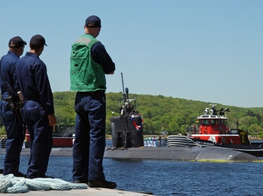 Line handlers await the arrival of the Virginia class attack submarine USS Hartford
