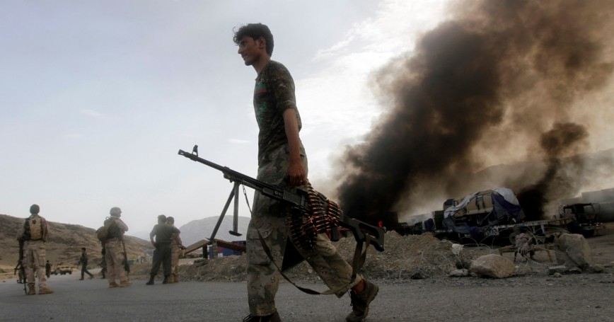 Afghan security forces leave the site of burning NATO supply trucks after an attack by militants near the Pakistani-Afghan border, June 19, 2014