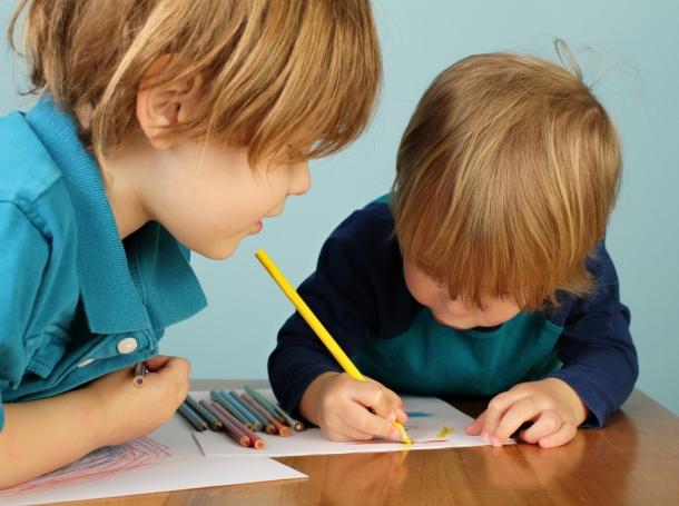 two preschool children using colored pencils