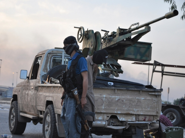 Fighters of the Islamic State of Iraq and the Levant (ISIL) stand guard at a checkpoint in Mosul, Iraq, June 11, 2014