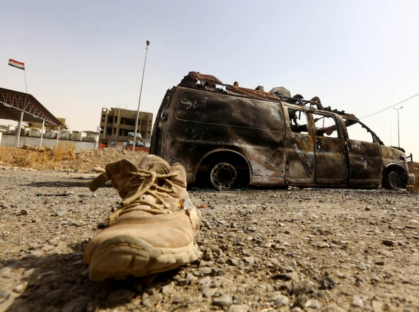 A burnt vehicle belonging to Iraqi security forces at a checkpoint in east Mosul, one day after radical Sunni Muslim insurgents seized control of the city, June 11, 2014