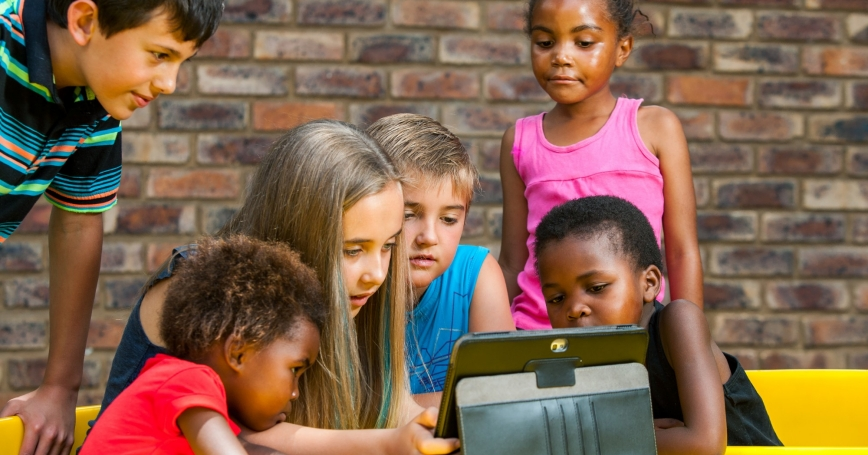 Diverse group of kids looking at tablet