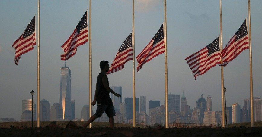 A man passes by the skyline of New York's Lower Manhattan and One World Trade Center as he walks through Liberty State Park in Jersey City, NJ