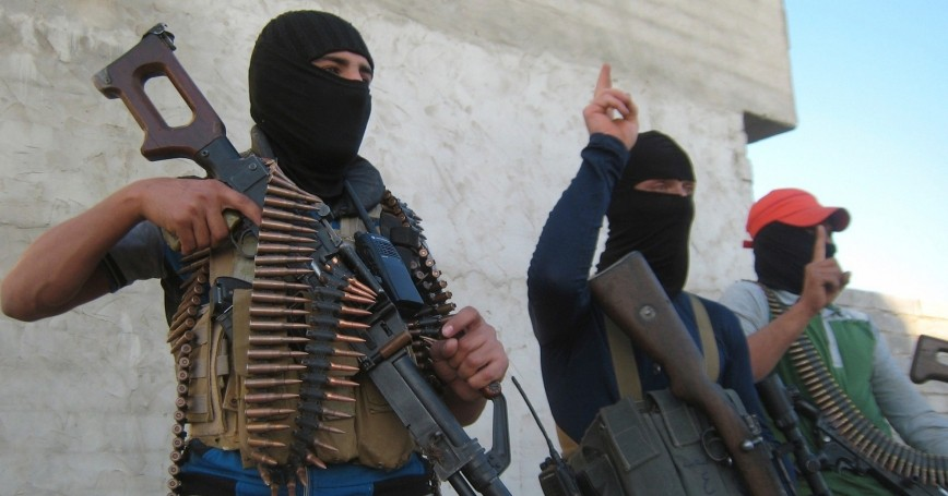 Masked Sunni gunmen pose with their weapons during a patrol outside the city of Falluja