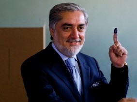 Afghan presidential candidate Abdullah Abdullah holds up his ink-stained finger as he casts his vote at a polling station in Kabul June 14, 2014