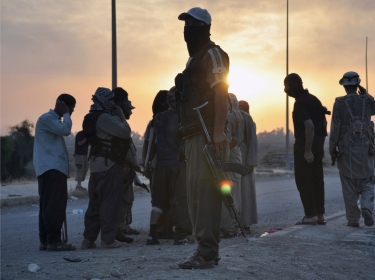 Fighters of the Islamic State of Iraq and the Levant (ISIL) stand guard at a checkpoint in the northern Iraq city of Mosul, June 11, 2014