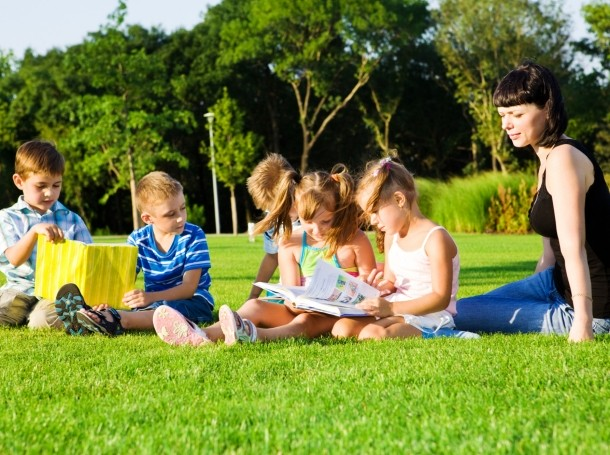 Teacher and preschool students reading outside