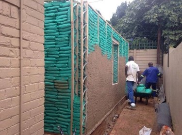 South African men create a sandbag building for EcoSteps
