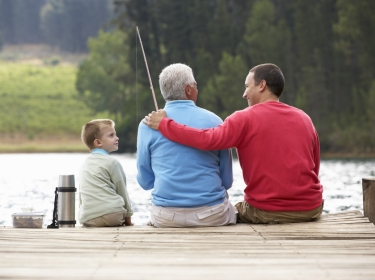 A son, father, and grandfather fishing from a dock