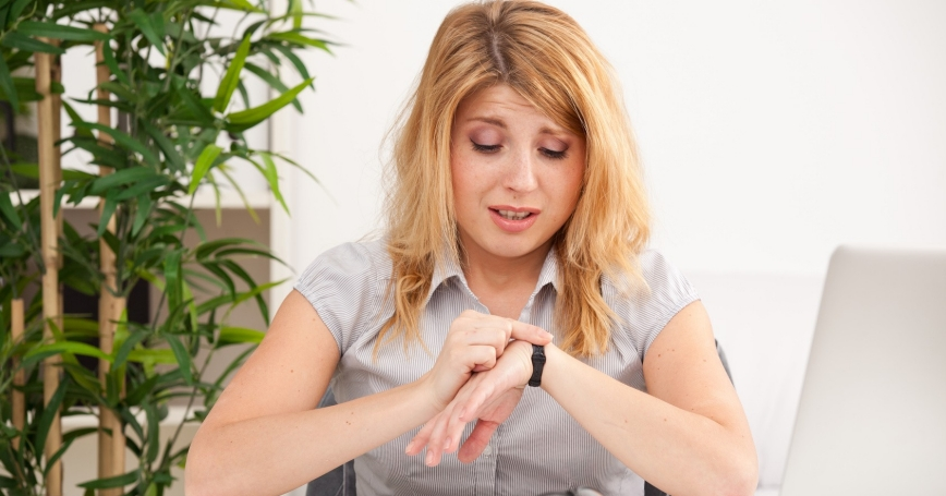 Woman sitting at a desk looking at her watch