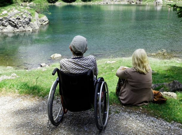 Man in wheelchair with caregiver, sitting by a lake