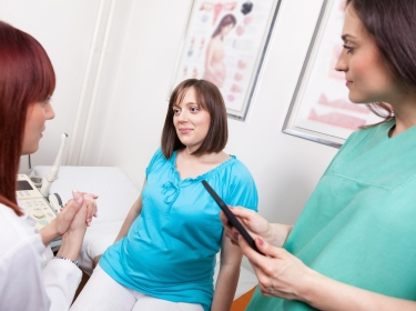 A pregnant woman in an exam room with a gynecologist and nurse