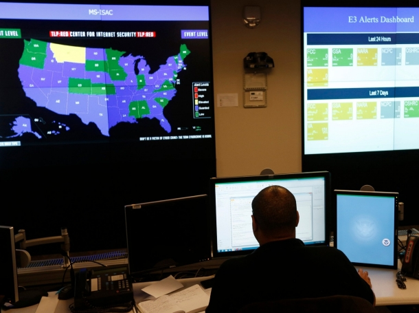 A U.S. Department of Homeland Security employee works in front of a U.S. threat level map and monitoring display